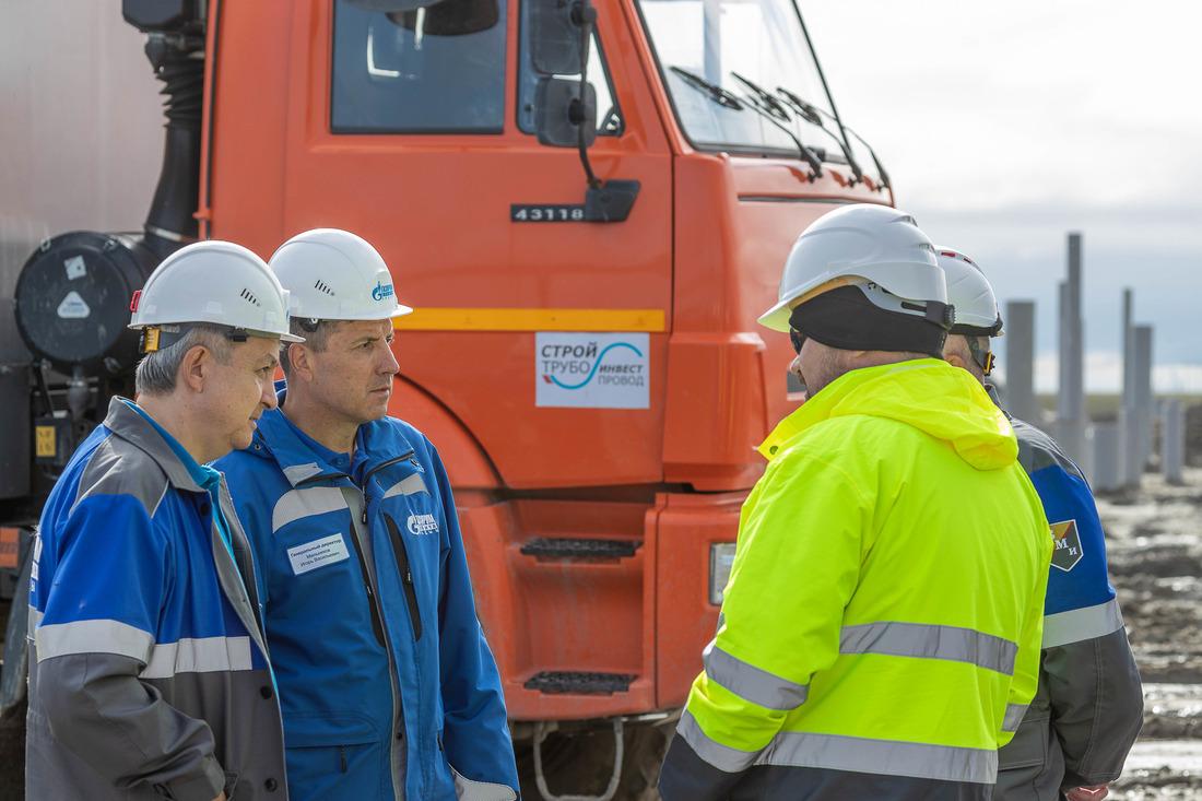 Генеральный директор ООО«Газпром добыча Надым» Игорь Мельников (второй слева) обсуждает сподрядчиками ход строительства объектов наХарасавэе